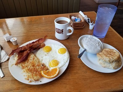 Three eggs, bacon, hash browns, and biscuits and gravy.