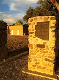 A view of the historical plaque itself and the Fort Lowell museum in the background.