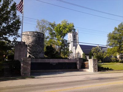"""The Tower"" is a community creation surrounded by park.  Looming behind it, we see the Christ Episcopal Church."