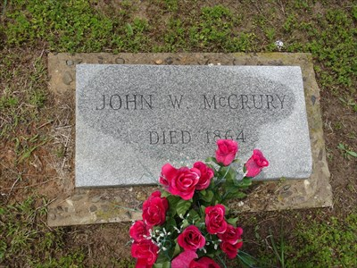 John W. McCrury, referenced on the historical marker as the first burial here