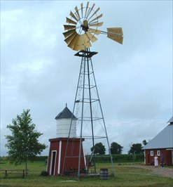View of windmill from NNE.  Water tank along side; barn in background.