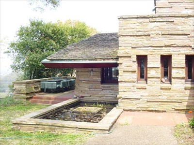 The raised patio to the front of the house, and the concrete patio scored in large squares adjacent to the house and water garden, are the quintessential Wright color, Taliesin Red.