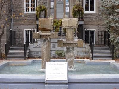 Bassin en ciment et deux colonnes de granits surmonté  de deux carrés irréguliers.