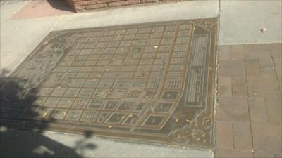 Embedded in the sidewalk.