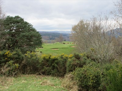 The final tee shot is through a narrow chute and over a deep gully containing the access road to the club car park.