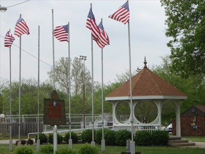 A distant image of the marker with the park and flags in the background