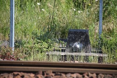 Un repère placé le long de la voie ferrée, juste avant la gare