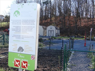 sign with garden plots in background