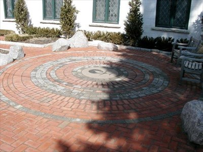 """The symbol of the Unitarian Universalist Society is in the center of the circle, surrounded by the inscription: """"We have associated ourselves together as seekers after truth and goodness""""."""