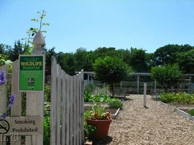 A sign at the gate identifies the garden as a certified wildlife habitat and the post in the middle of the path marks the garden as #2 on the self-guiding tour of Ferry Farm.