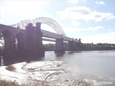 The arch belongs to the road bridge behind the rail bridge