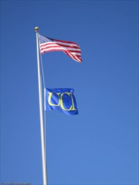 Image of the American flag flying on the campus of California Irvine.