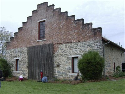 Volunteers work on landscaping in front of this historic barn.