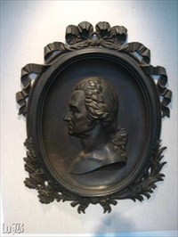 A profile bust of George within a frame of ribbons and foliage hangs at the Ferry Farm Visitor Center.
