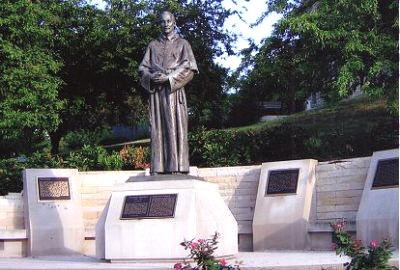 The German plaque is on the left-rear, past the statue.