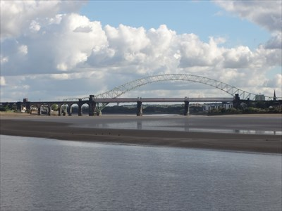 The large arch structure is actually the road bridge on the far side of the bridge and dwarfs the rail bridge