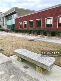 The bench is located at the nortwest end of a narrow green space behind the Jesse M. Smith Memorial Library.