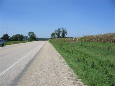 Looking west along County Highway M, the station is at the white notebook and witness posts, right-center.