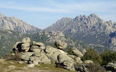 Tras el conjunto de rocas, al fondo, el collado de la Dehesilla y, a la derecha, el domo de el Yelmo.
