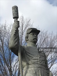 Detail: The upper torso of the sculpted soldier holding an artillery rammer and sponge.