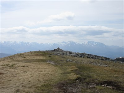 Ben Nevis and its surrounding ranges are in the distance beyond the cairn.