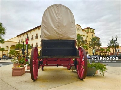 Visible beyond a covered wagon, the La Reina Clock at Spanish Springs Town Square is in The Villages, Florida.