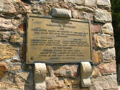 A bronze plaque is mounted on the front of the stone tower listing the names of the first settlers in the area.