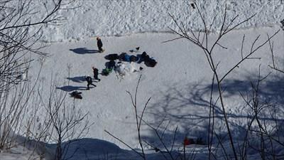 Les grimpeurs au bas se préparent à escalader la paroi glacée.