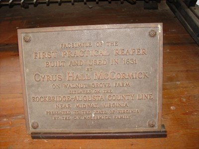 This plaque sits in front of the replica of the first reaper