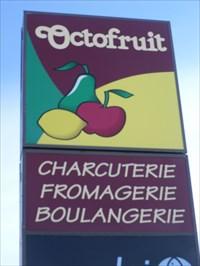 Enseigne près du trottoir et de la rue de  Épicerie Octofruit.  Illuminated sign near the sidewalk and the street Grocery Octofruit.