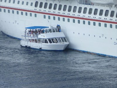 Tender boat next to cruise ship. This is the mode of transport between the ship and the Watler terminal.