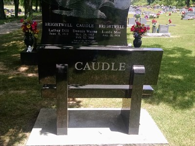 Dennis Wayne Caudle dedicated bench, by MountainWoods.  Back of bench in foreground with massive and ornate headstone in the background.
