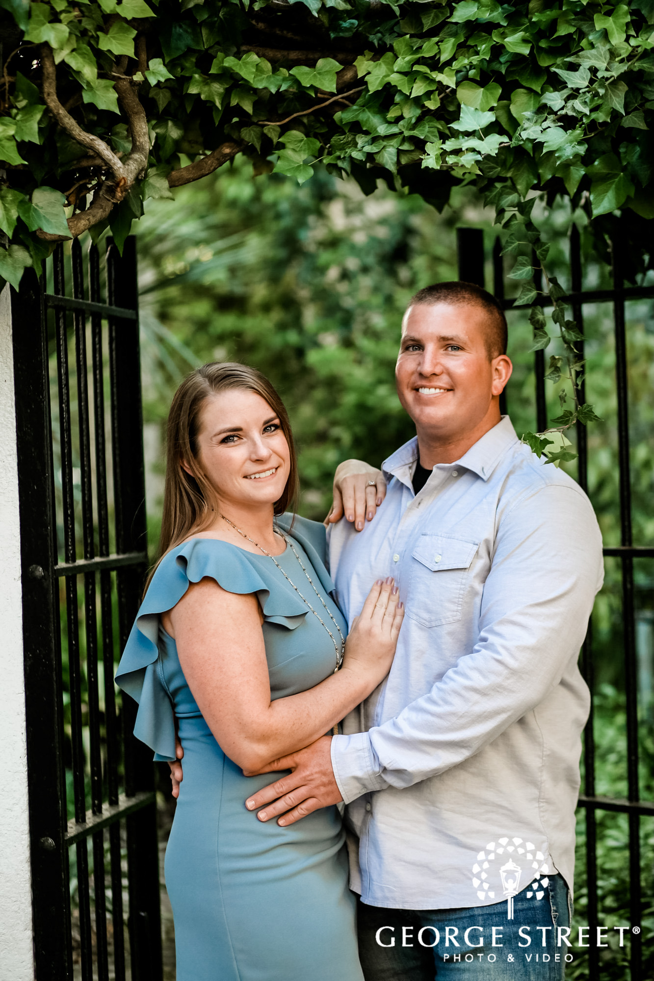 blissed couple with iron fence in charleston engagement photo