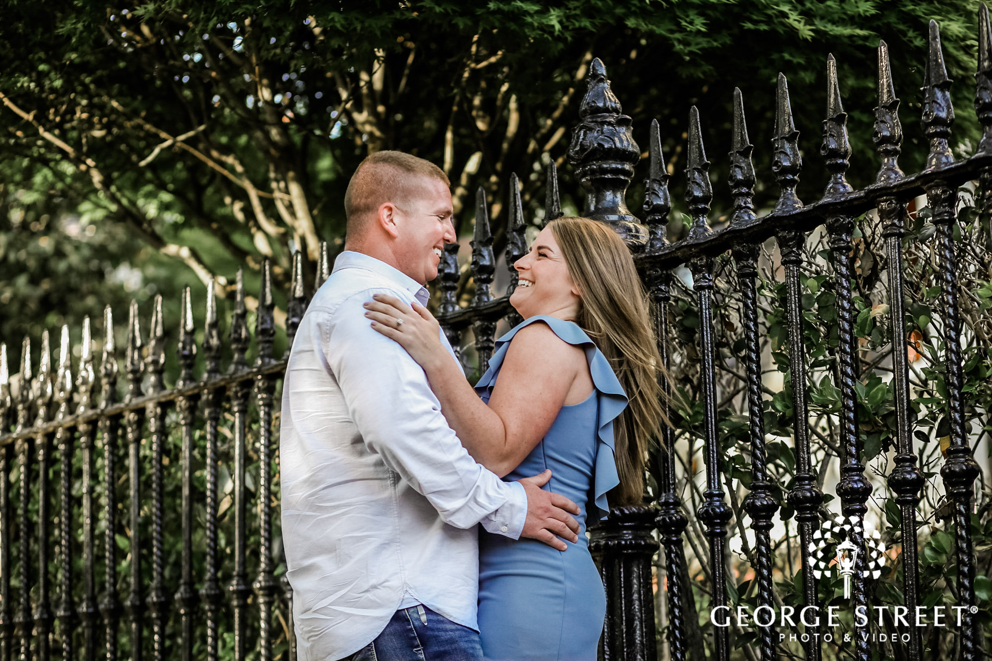 happy couple on pathway to white point garden in charleston engagement photos 2