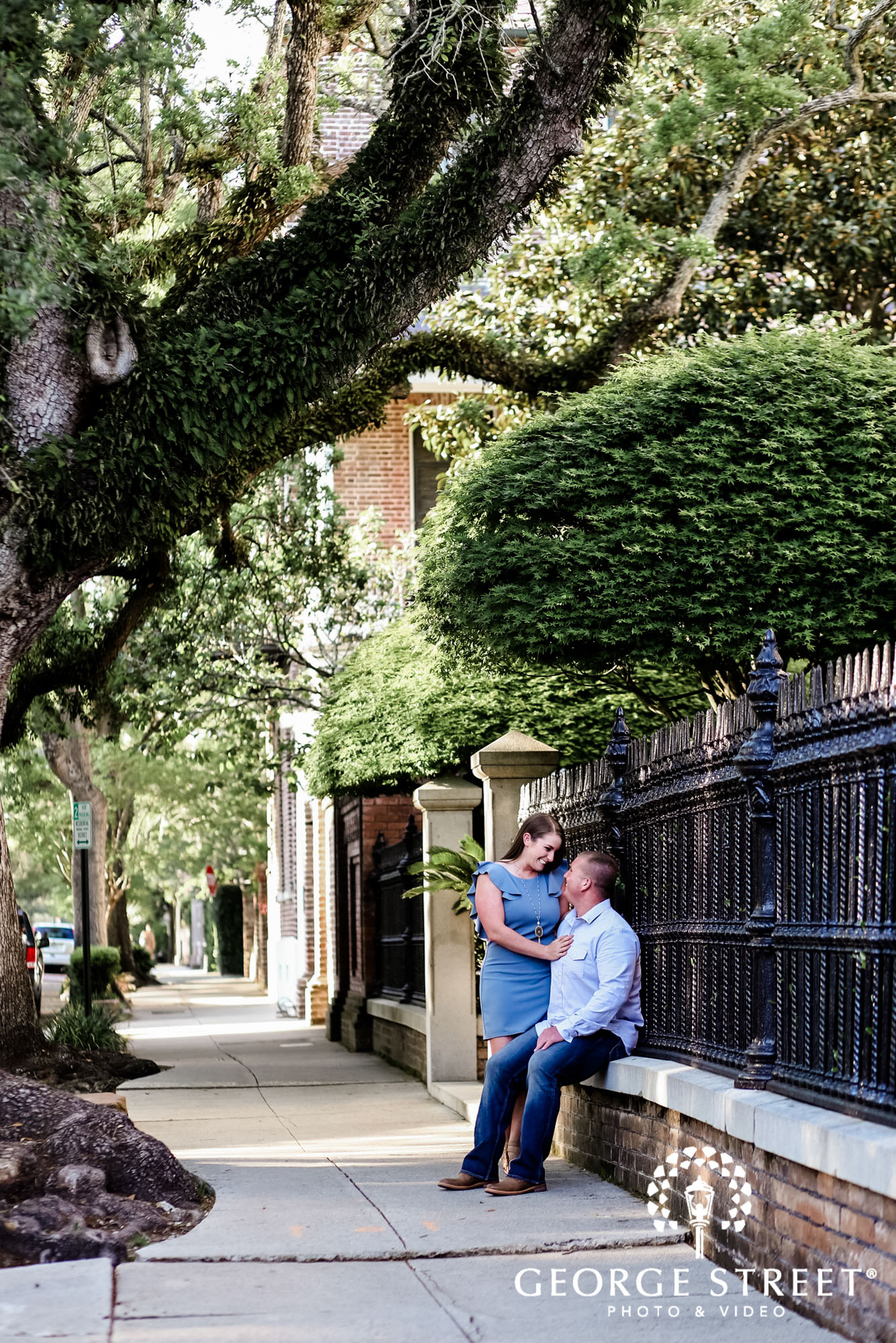happy couple on pathway to white point garden in charleston engagement photos