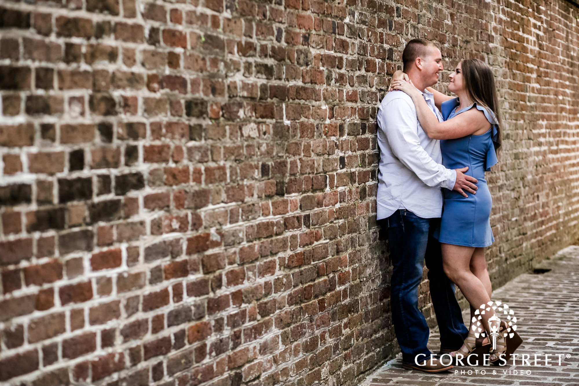 loving couple with red bricks wall in charleston engagement photos 2