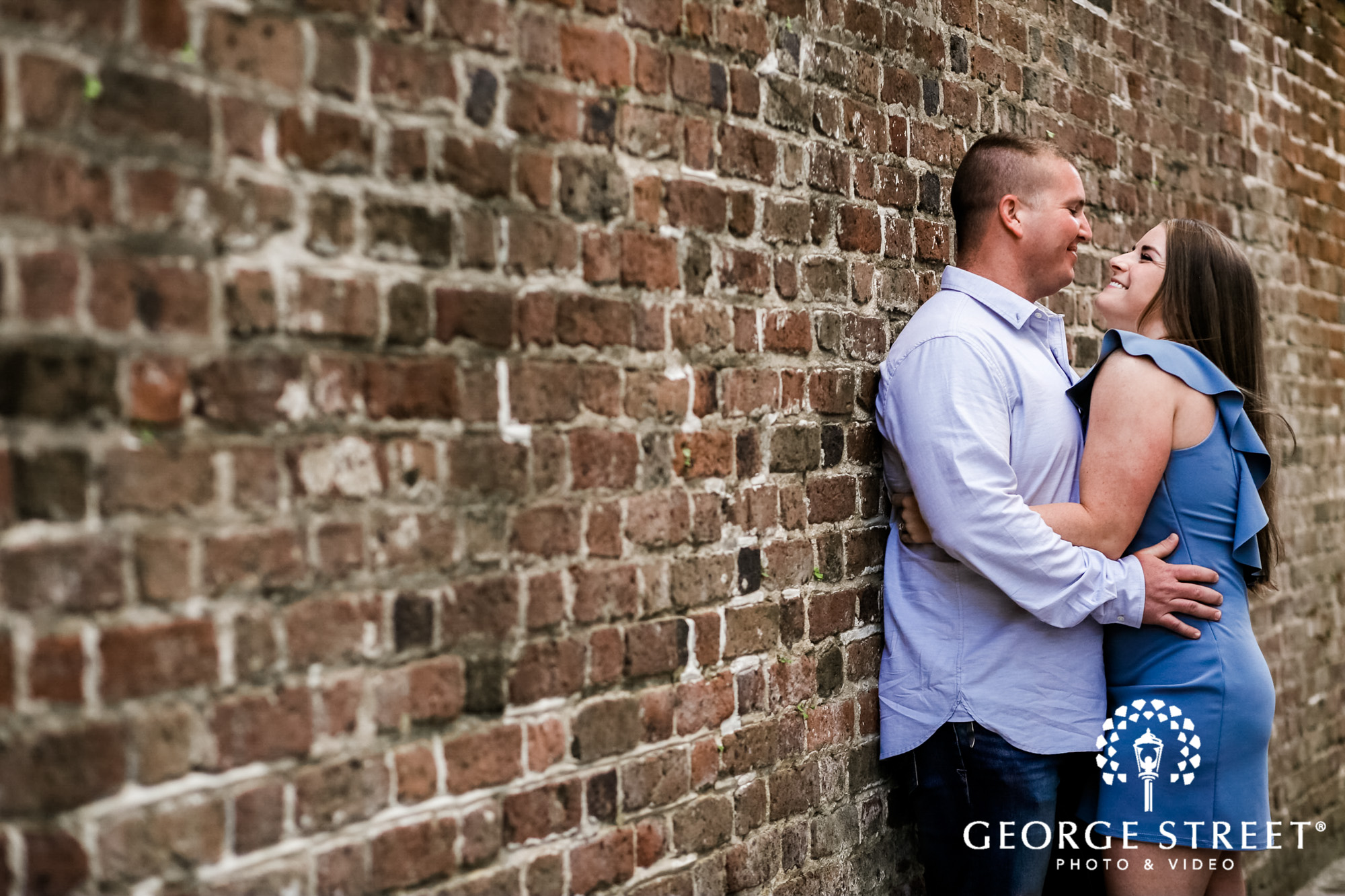 loving couple with red bricks wall in charleston engagement photos 3