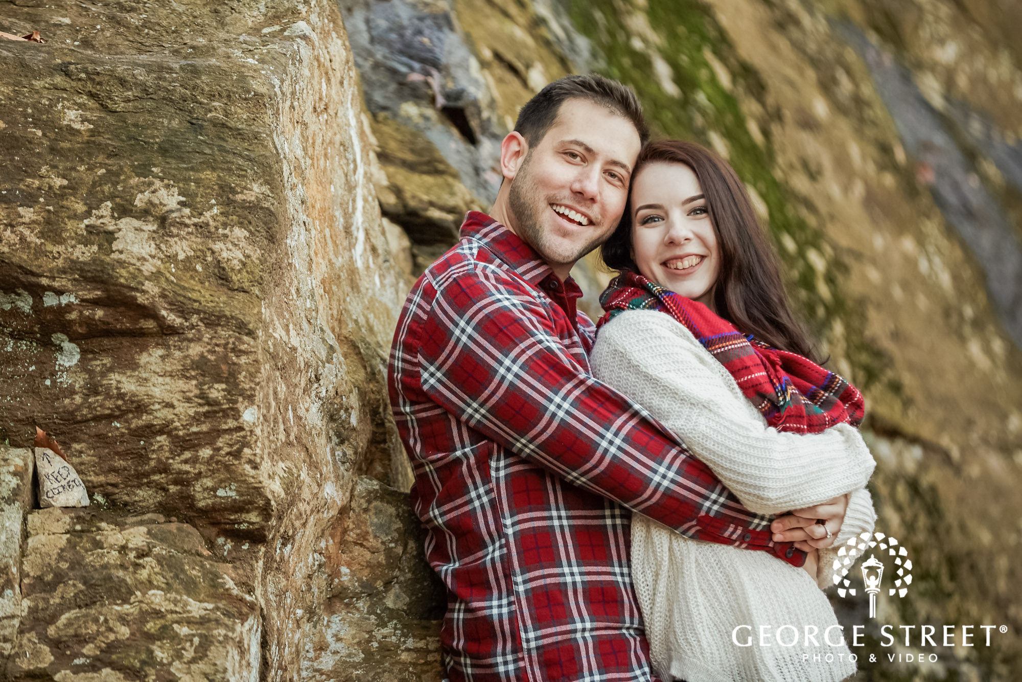 cute couple in front of rock wall engagement photo