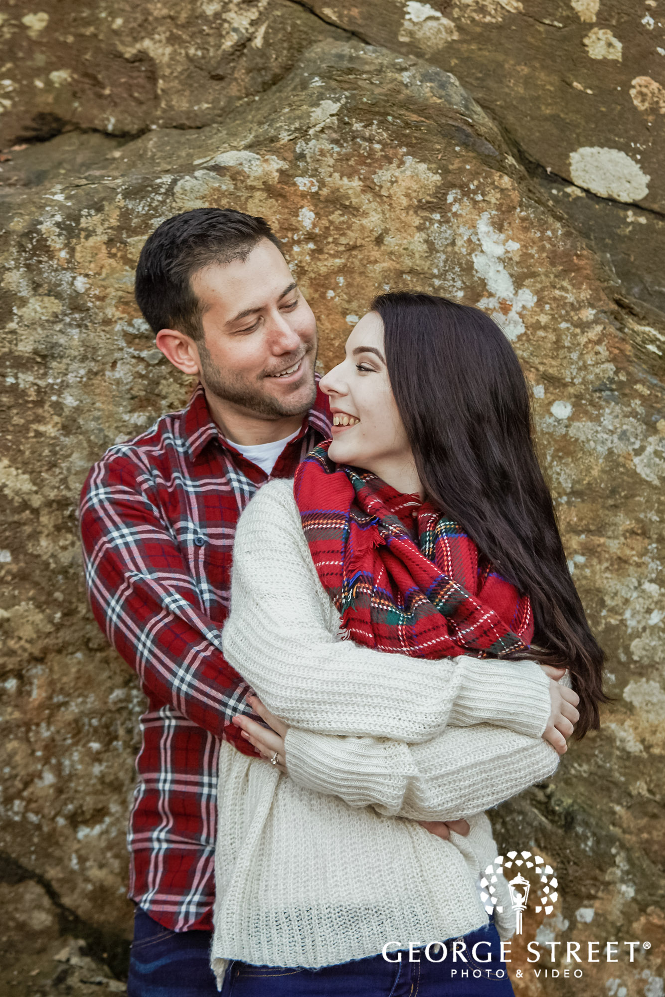 lovely couple in front of rock wall engagement photo