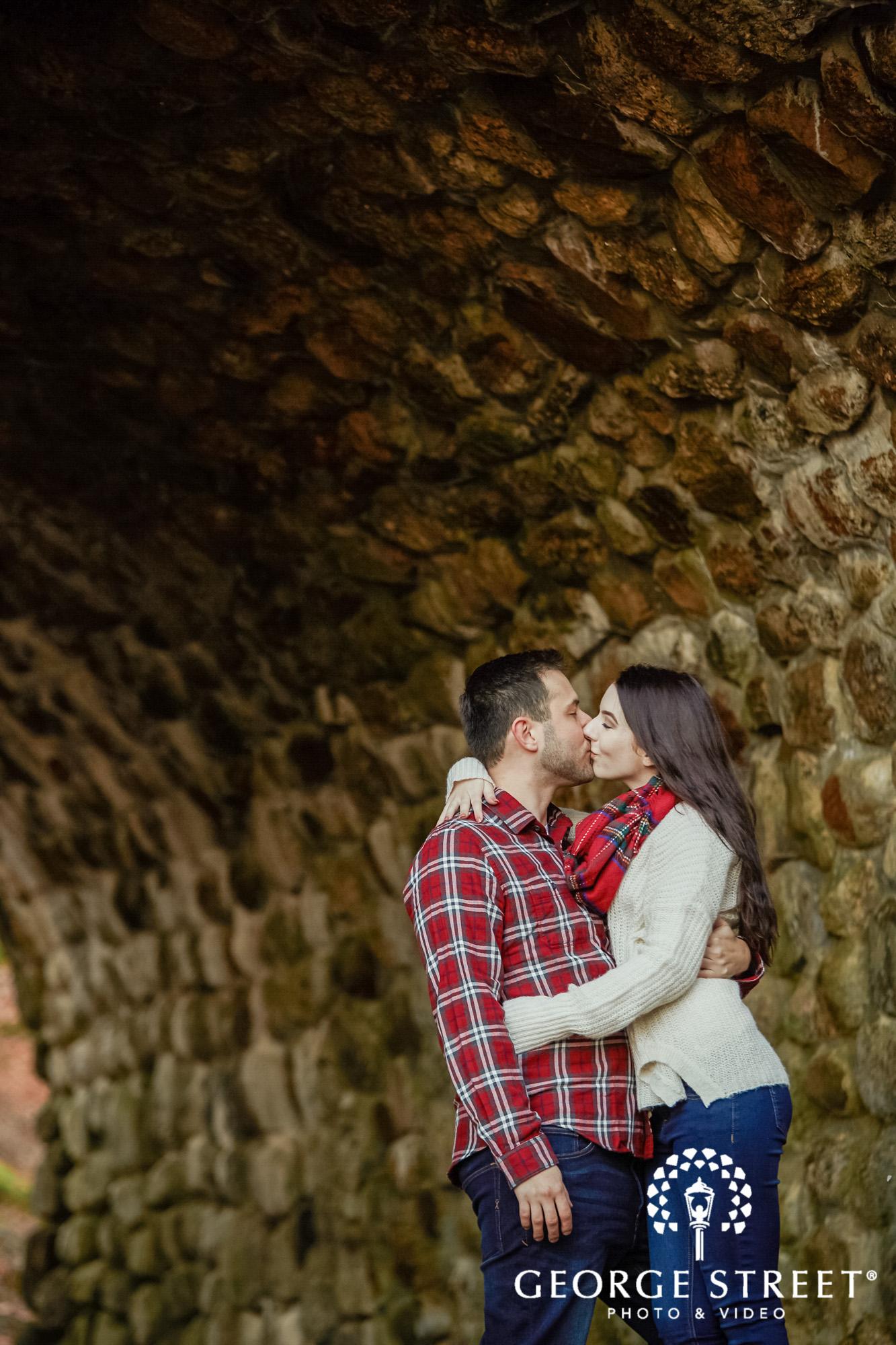 passionate couple near stone wall engagement photo
