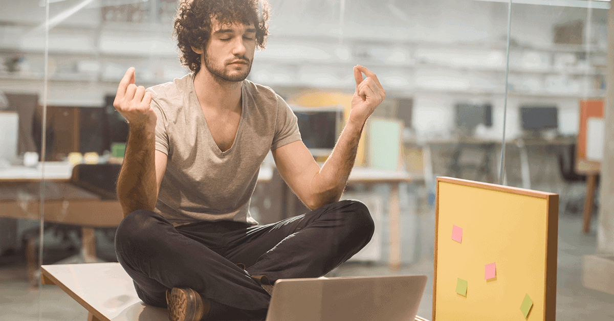 Young entrepreneur tries to meditate to become more productive at work