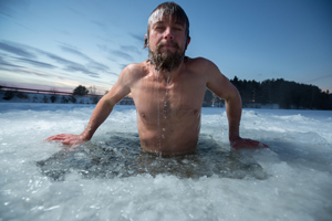 man bathing in ice hole