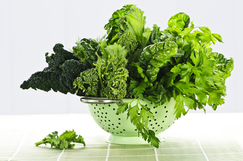 Dark green leafy fresh vegetables in metal colander collagen
