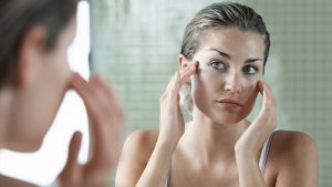 women looking in mirror collagen skin care