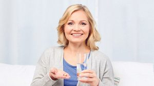 middle aged woman taking collagen supplement