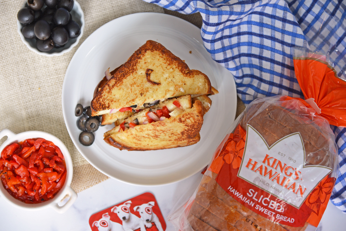 Delicious melted cheeses with roasted red pepper, black olives and red onion on two slices of King's Hawaiian Bread and tzatziki sauce. #greekcheesemelt #grilledcheese www.savoryexperiments.com