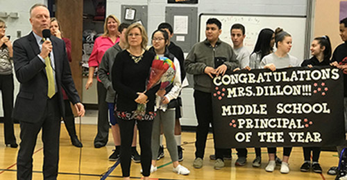Dr. Martirano and Cynthia Dillon standing in gymnasium with students holding banner that reads congratulations.