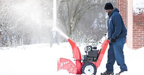 HCPSS grounds staff using a snowblower to prepare for school opening after a heavy snowstorm.
