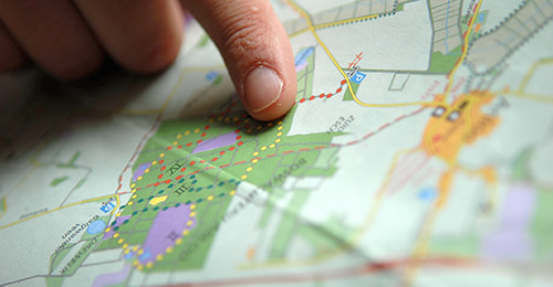 Finger pointing to a region on a map.