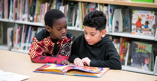 Two students reading in a classroom.